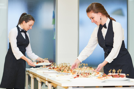 Catering. Restaurant waitress serving table with food Stock Photo
