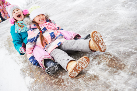 children having fun riding ice slide in winter Reklamní fotografie