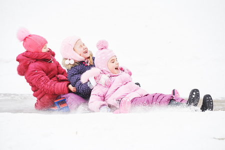 children having fun riding ice slide in winter Stock Photo