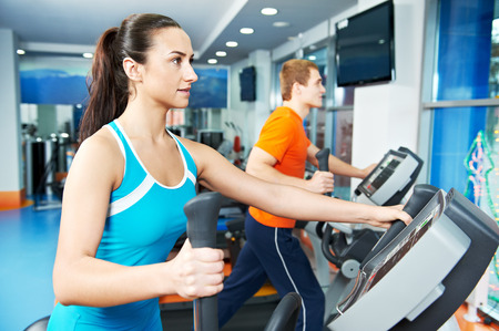 Cardio training. Woman and man at cross-trainers in gym