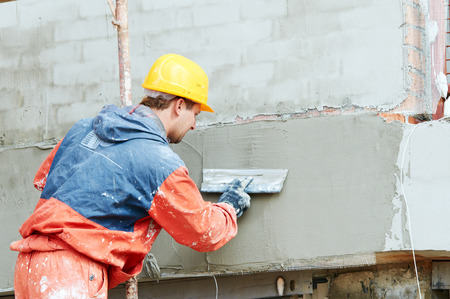 facade work. builder plastering outside wall with putty knife float