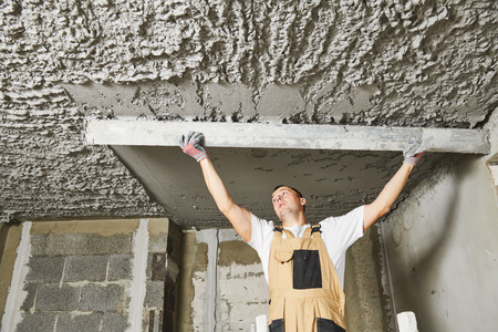 Plasterer smoothing plaster mortar on ceiling with screeder Stock Photo