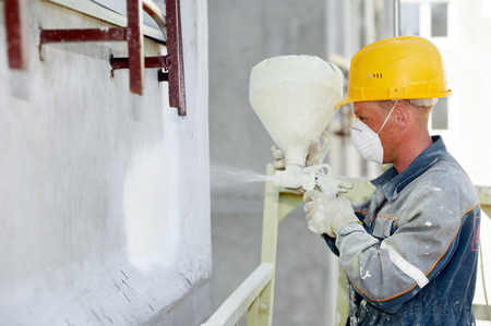 Facade work. Worker painting by spreading white paint Stock Photo