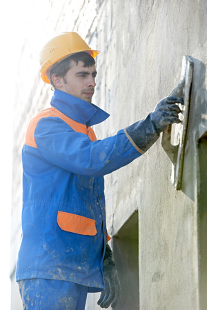 builder at facade plastering work with putty knife float Stock Photo