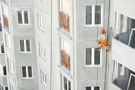industrial climber. Builder sealing outside facade building seam joints with insulation mastic Stock Photo
