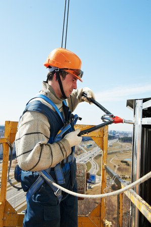Worker builder at facade installation work with riveting hammer Stock Photo