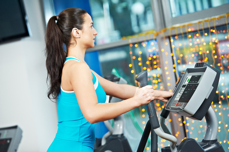 Cardio training. Woman at cross-trainers in gym