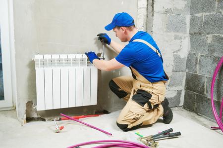 plumber at work. Installing water heating radiator Stock Photo