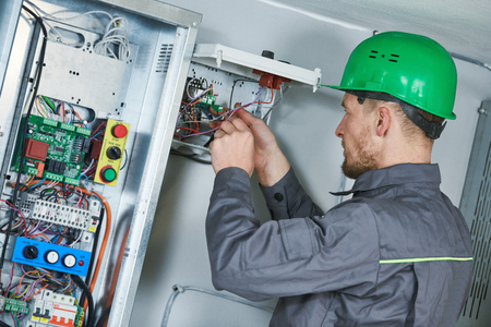 Electrician make maintenance in engine room of elevator Stock Photo