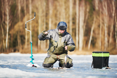 winter fishing on ice. fisherman or angler hooking the fish