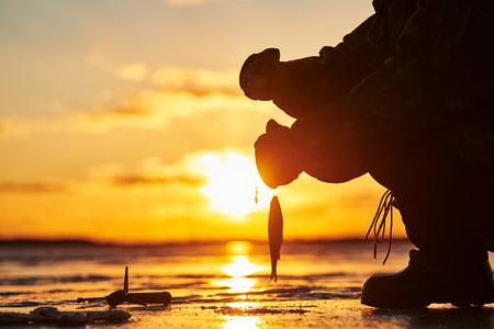 The angler fisherman at ice winter fishing. Sunset