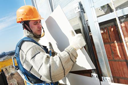 facade builder installing tile on wall