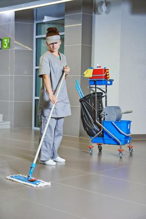 impresa di pulizie. La donna pulisce il pavimento con il mop