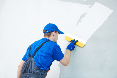 refurbishment. Plasterer worker spackling a wall with putty Banque d'images