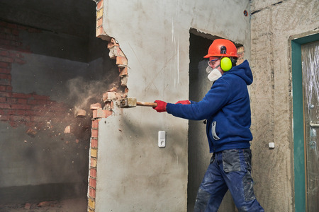 demolition work and rearrangement. worker with sledgehammer destroying wall Standard-Bild
