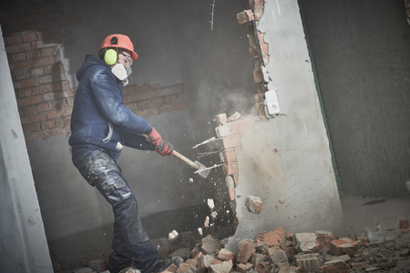 demolition work and rearrangement. worker with sledgehammer destroying wall 版權商用圖片