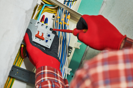 Electrician works with switchbox