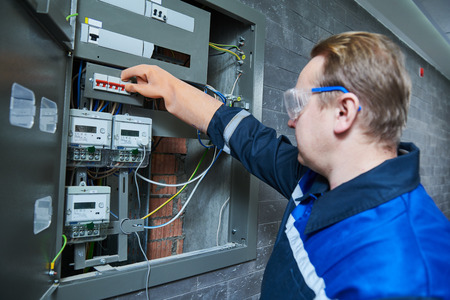 Electrician works in fuse box. Switching of circuit breaker
