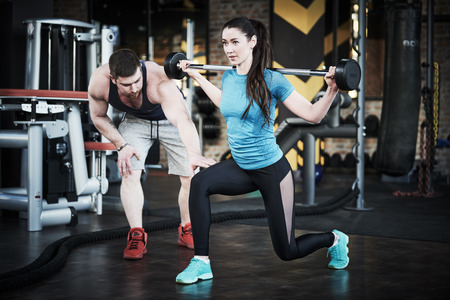 Personal trainer man helps woman work with barbell at squat exercises in gym