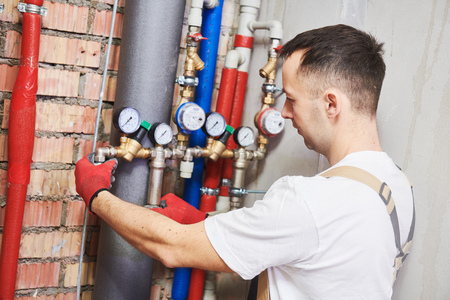 plumber installing and mounting water equipment - meter, filter and pressure reducer
