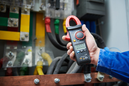 Electrician work concept. Hand with multimeter tester in switchbox Reklamní fotografie