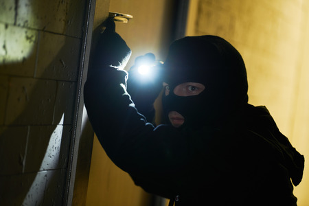 Burglar thief in mask. break-in of an apartment. 스톡 콘텐츠