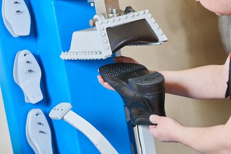 Shoemaker repair shoe. Pressing the sole for male footwear Reklamní fotografie