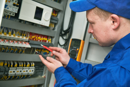 Electrician works with tester in switchbox