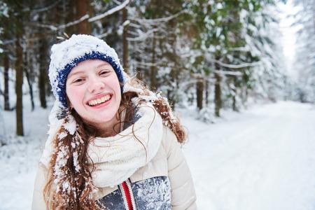Portrait of happy smiling girl in winter snowy forest Reklamní fotografie