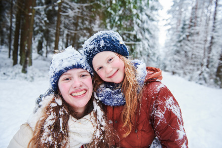 Portrait of happy smiling girls in winter snowy forest