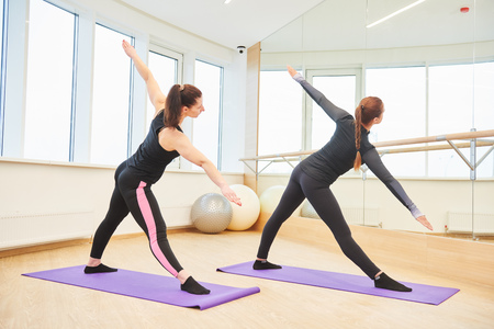 yoga training. Instructor and woman doing excercise