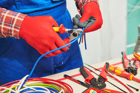 Electrician works with cable. hands with Cable Shears