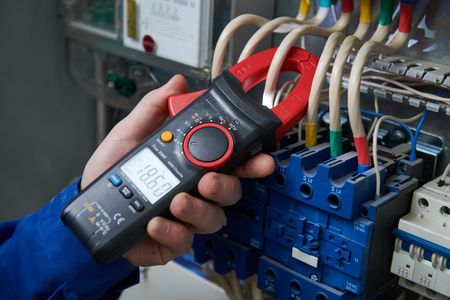 Electrician work concept. Hand with multimeter tester in switchbox Stok Fotoğraf