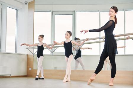 Balletttänzer trainiert kleines Ballerina-Mädchen Standard-Bild