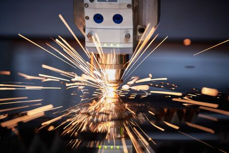 Laser cutting. Metal machining with sparks on CNC laser engraving maching Stock Photo