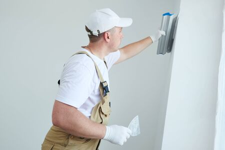 Painter with putty knife. Plasterer smoothing wall surface at home renewal Stock Photo