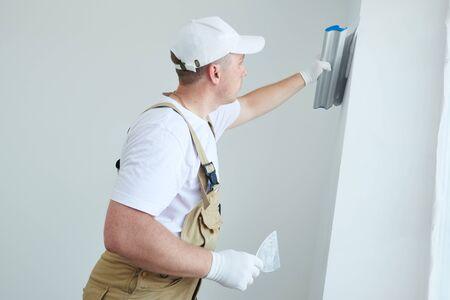 Pintor con espátula. Yesero alisar la superficie de la pared en la renovación del hogar Foto de archivo