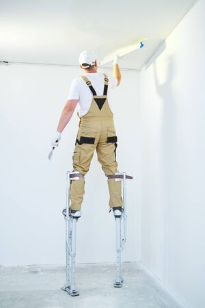 Painter in stilts with putty knife. Plasterer smoothing ceiling surface at home renewal Standard-Bild