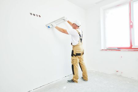 Painter with putty knife. Plasterer smoothing wall surface at home renewal