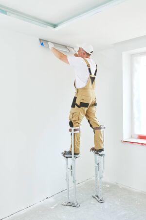 Maler auf Stelzen mit Spachtel. Gipser Glätten der Deckenfläche zu Hause Erneuerung Standard-Bild