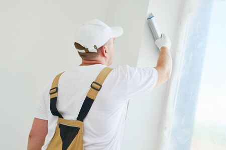 Painter with putty knife. Plasterer smoothing esconson surface at home renewal Stockfoto
