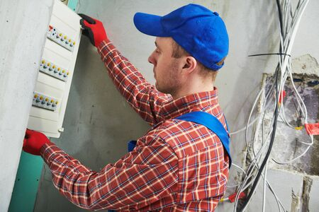 Electrician works with pliers in switchbox. current breaker installation