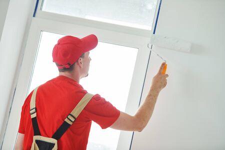 Travailleur de peintre avec la surface de mur de peinture de rouleau en blanc