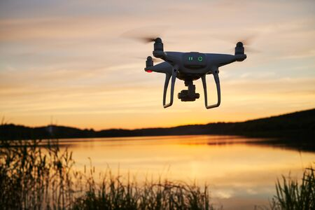 drone quadcopter with digital camera flying at sunset Stockfoto