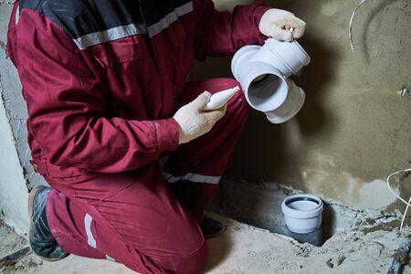 Trabajador de fontanero instalando tuberías de alcantarillado en el sistema de alcantarillado