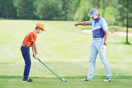 Boy playing golf in summer with trainer Stock fotó