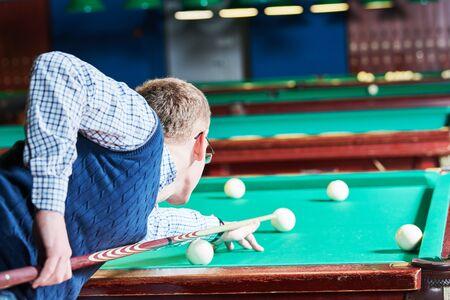 man playing billiards in club