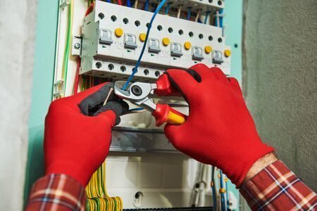 Electrician works with shears cutter in switchbox Stok Fotoğraf