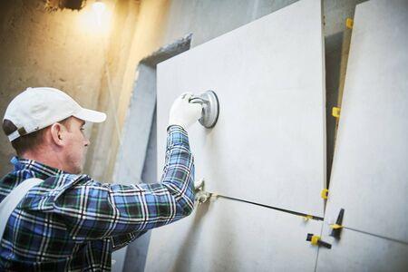 Solador instalando baldosas de gran formato en pared. Renovación de casa en interiores Foto de archivo