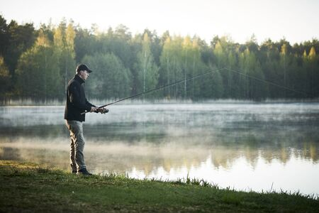 fishing. fisher with spinning rod early morning Banque d'images